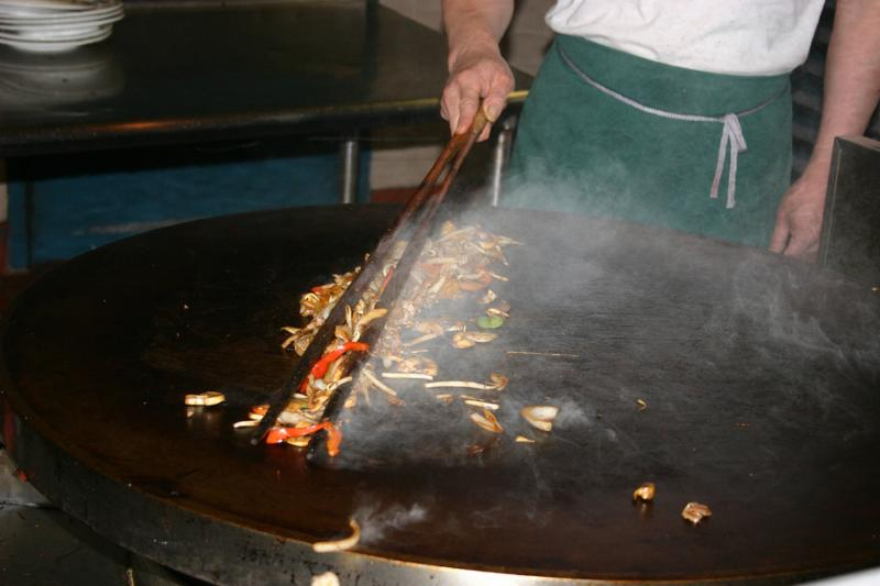 An Asian chef carrying out his artistry on a large round grill which I really enjoyed later