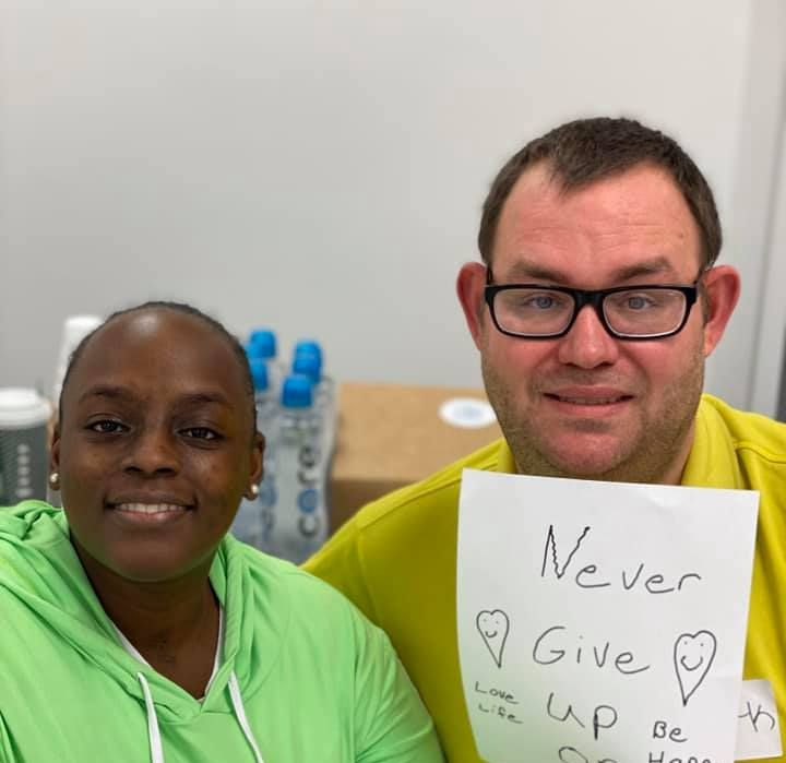 Advocates at a Statewide Listening Tour Session smiling and holding up a sign that states Never Give Up.