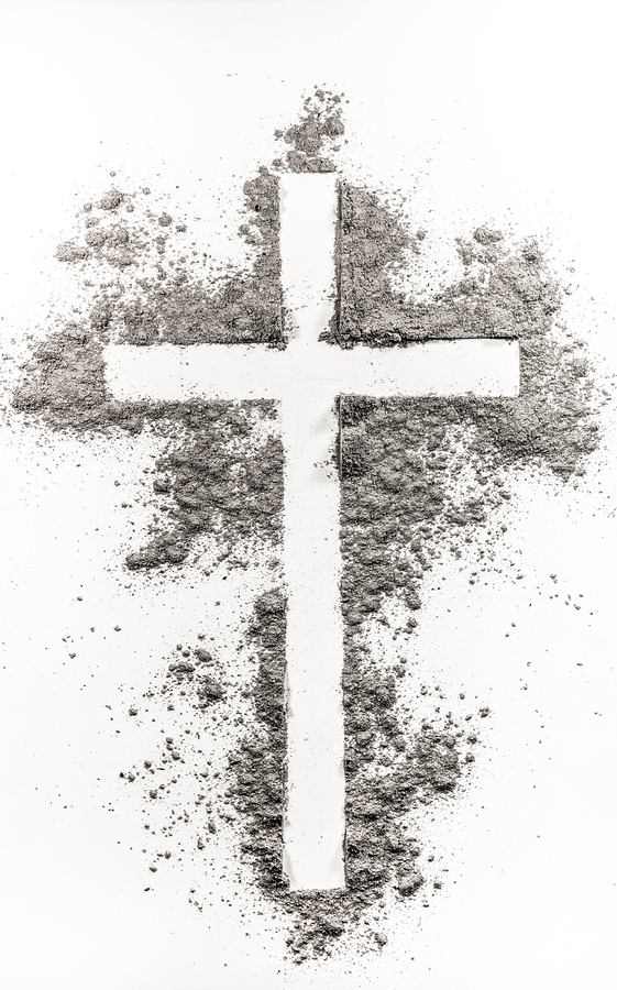 Christian cross made of ash on a white background