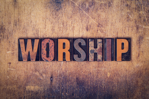The word  Worship  written in dirty vintage letterpress type on a aged wooden background.