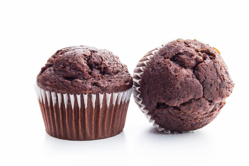 The tasty chocolate muffin isolated on white background.