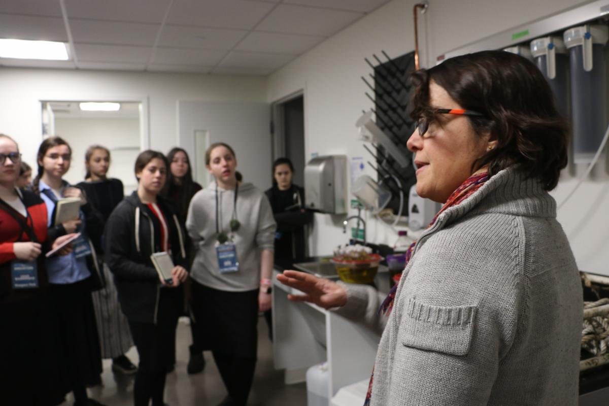 MIT Sea Grant Research Scientist Carolina Bastidas speaks to a group of female high school students in a lab