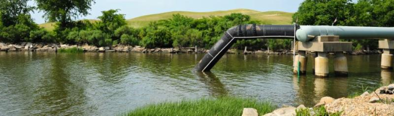 A pipe for wastewater outfall entering a large body of water