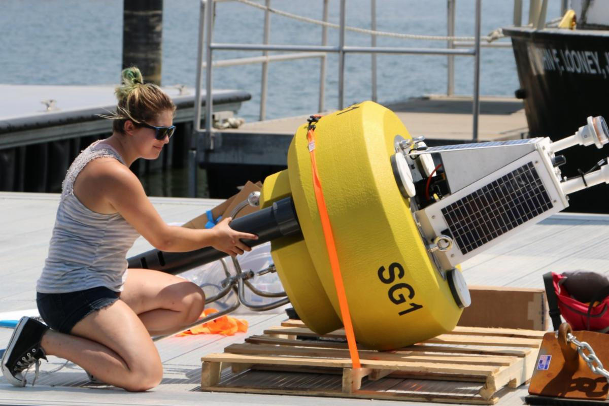 A female student with a data buoy on a boat dock