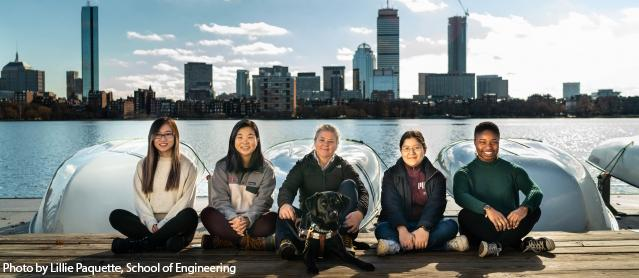 Four students sitting with MIT employee and her seeing eye dog on the boat dock on then Charles River with boats and the Boston skyline behind them