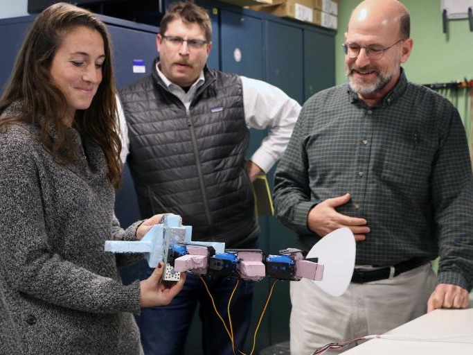Science educators from The Governor's Academy holding a robotic fish from a freshman course component led by Dr. Tom Consi.