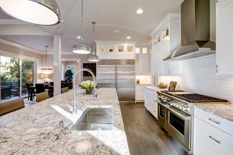 White kitchen design features large bar style kitchen island with granite countertop illuminated by modern pendant lights. Stainless steel appliances framed by white shaker cabinets . Northwest USA