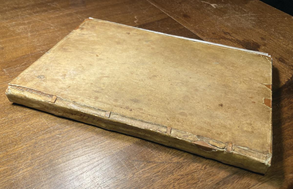 Closed letter book with a light brown cover and sewn repairs visible on the binding.