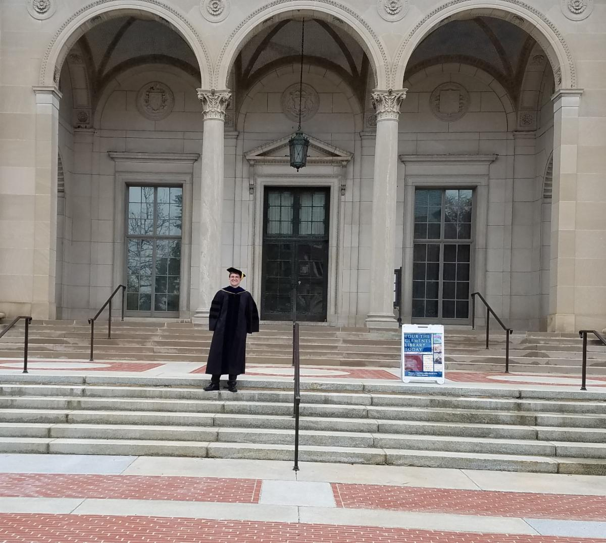 A new graduate stands in cap and gown on the front steps of the Clements Library.