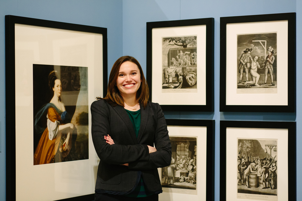 Allison Lange smiles, arms crossed, posing in front of a blue wall with framed historic images.