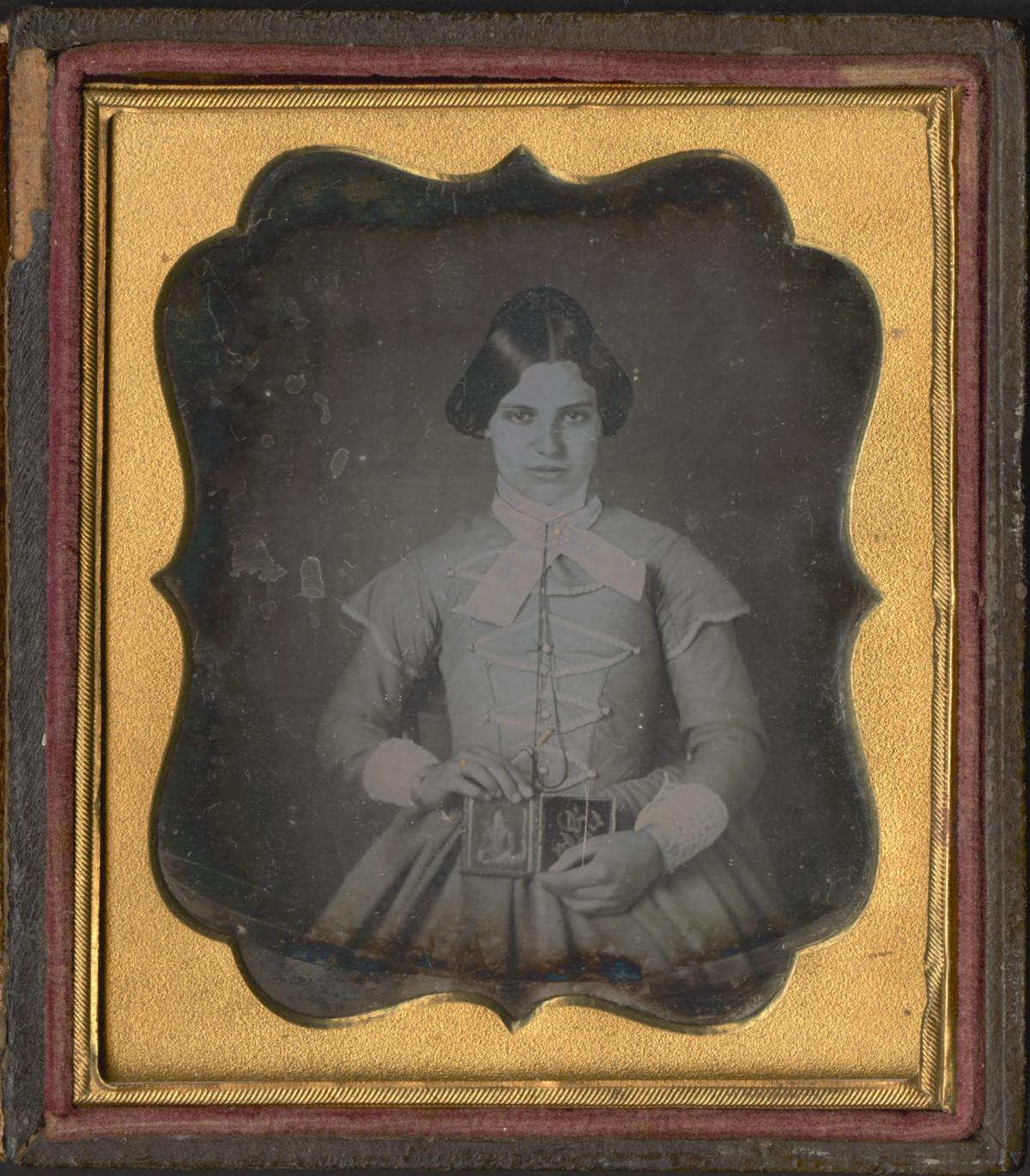 Young woman holding cased daguerreotype portrait. / May 9 1851 Taken By S. C. Smith, Fentonville, Mich.
