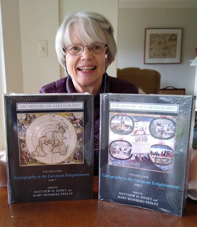 "Mary Pedley smiles and holds ""The History of Cartography, Vol. 4"" parts 1 and 2"