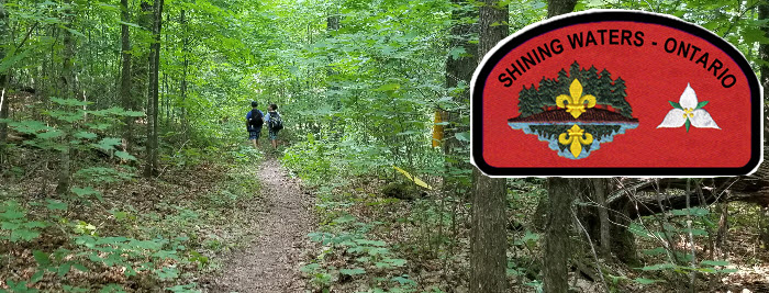 Shining Waters Council Stock Banner showing Scouts walking a forest trail.  Image from Haliburton Scout Reserve Summer 2018.