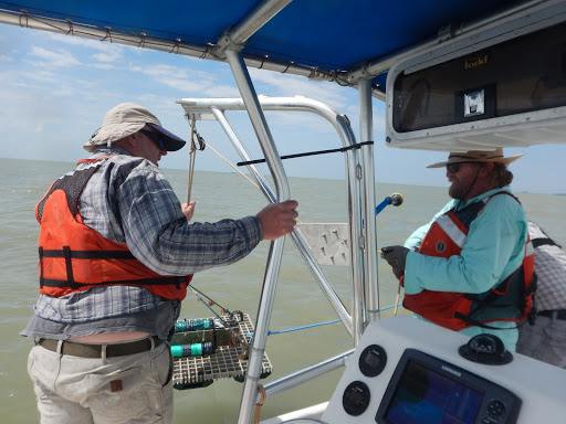A NOAA field crew deploys a shallow-water sensor in South Texas waters for a current survey.