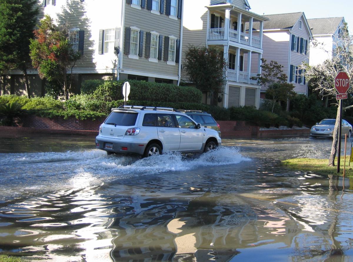 Car driving through a flooded street.