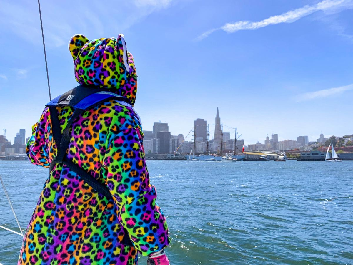 Person in a neon leopard suit wearing a PFD and looking at the San Francisco City Front from the deck of a sailboat.