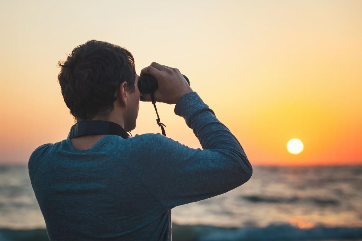 Man scanning the horizon with binoculars