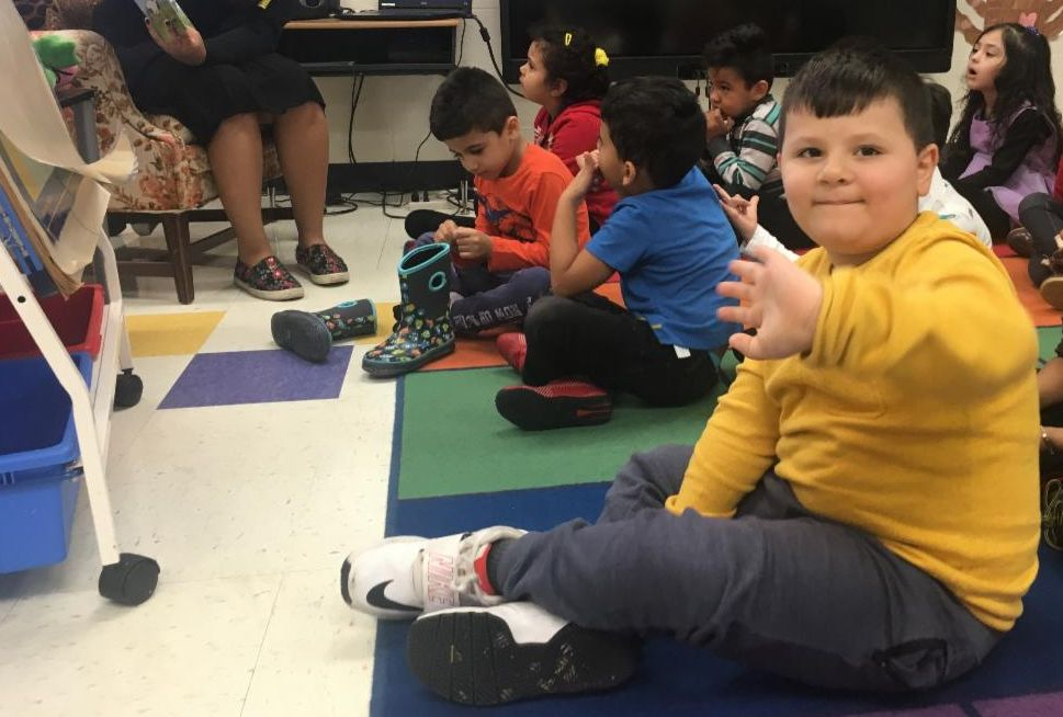 A child in a Pre-K classroom wearing a yellow sweatshirt waves at the camera