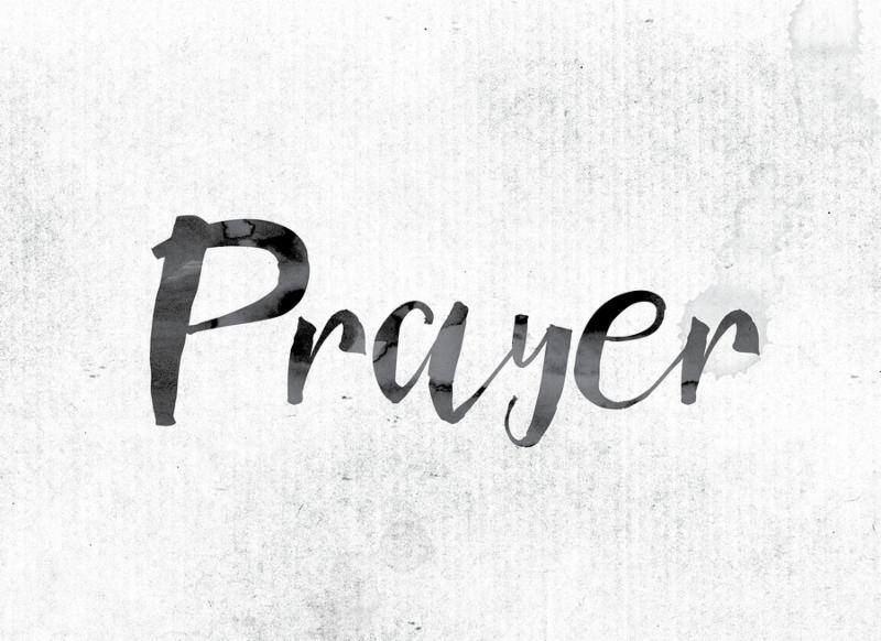 The word  Prayer  concept and theme painted in watercolor ink on a white paper.