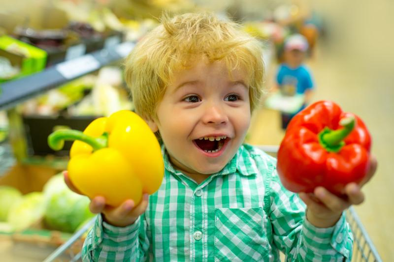 Happy vegetables child. Cute kid in supermarket holds bulgarian sweet pepper for salad. Healthy food fresh vegetables for lunch. Shopping in store fresh products for kitchen and cooking. Baby food