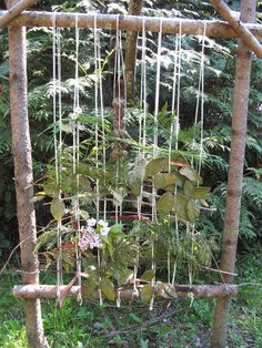Photo of a wooden branch square frame with string running top to bottom and various plant branches woven horizontally