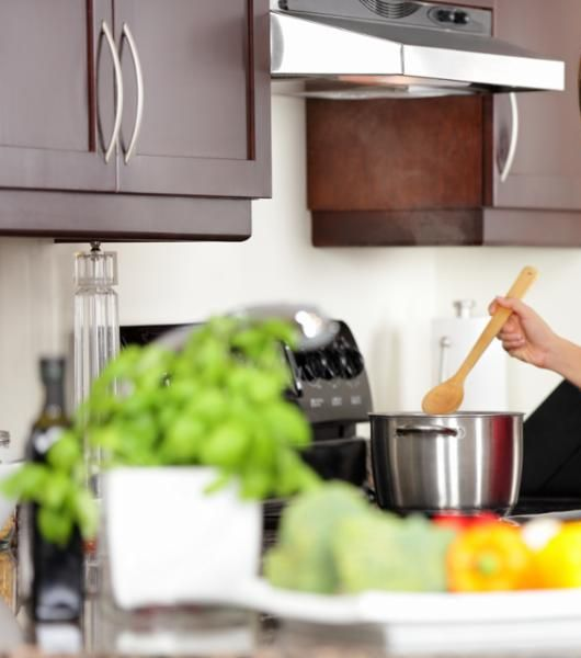Image of someone stirring food in a pot in the background, with fresh produce on the counter in the foreground