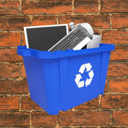 Image of a blue recycling bin willed with electronics againgst a brick backdrop