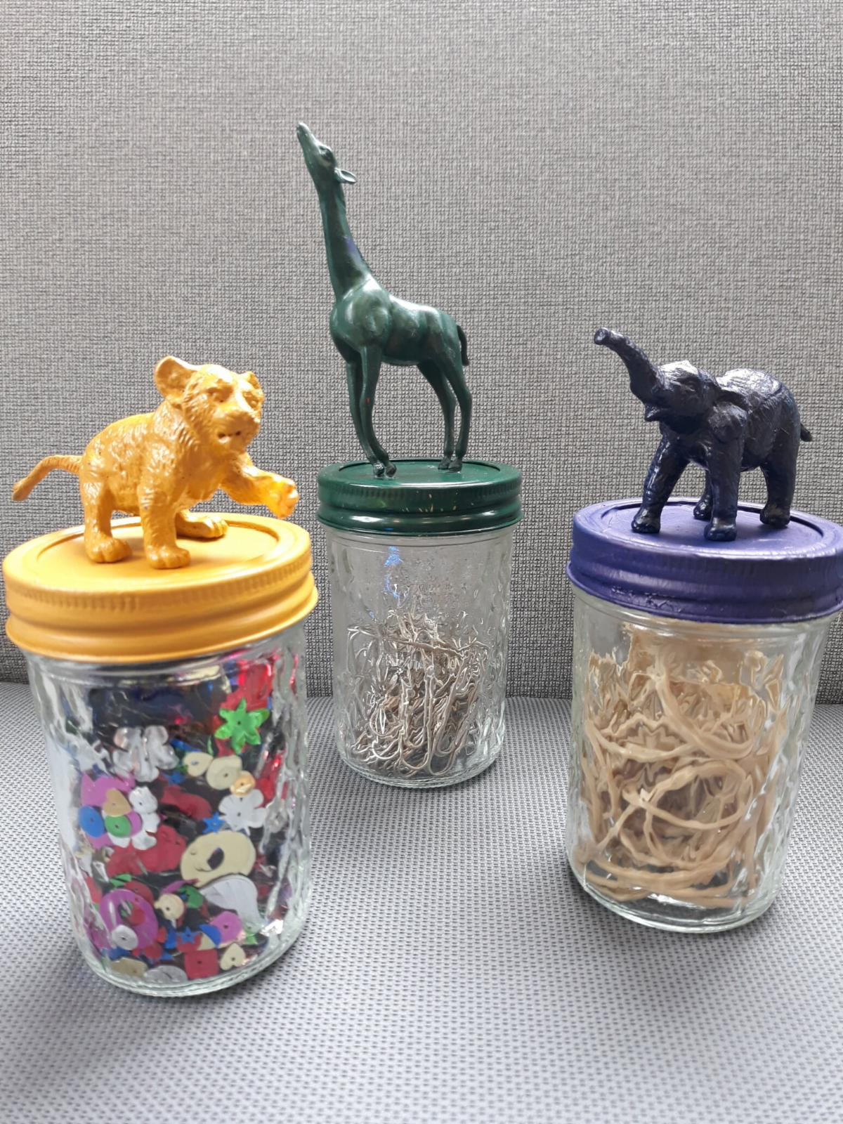 Image of glass jars with painted lids and painted plastic animals on top