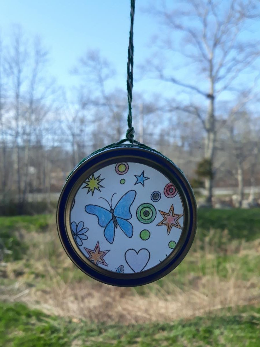 Picture of a suncatcher with butterflies and other shapes hanging in a window.