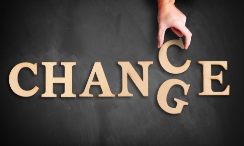 hand is moving a wooden letter_ turning the word  change  to  chance  on a blackboard