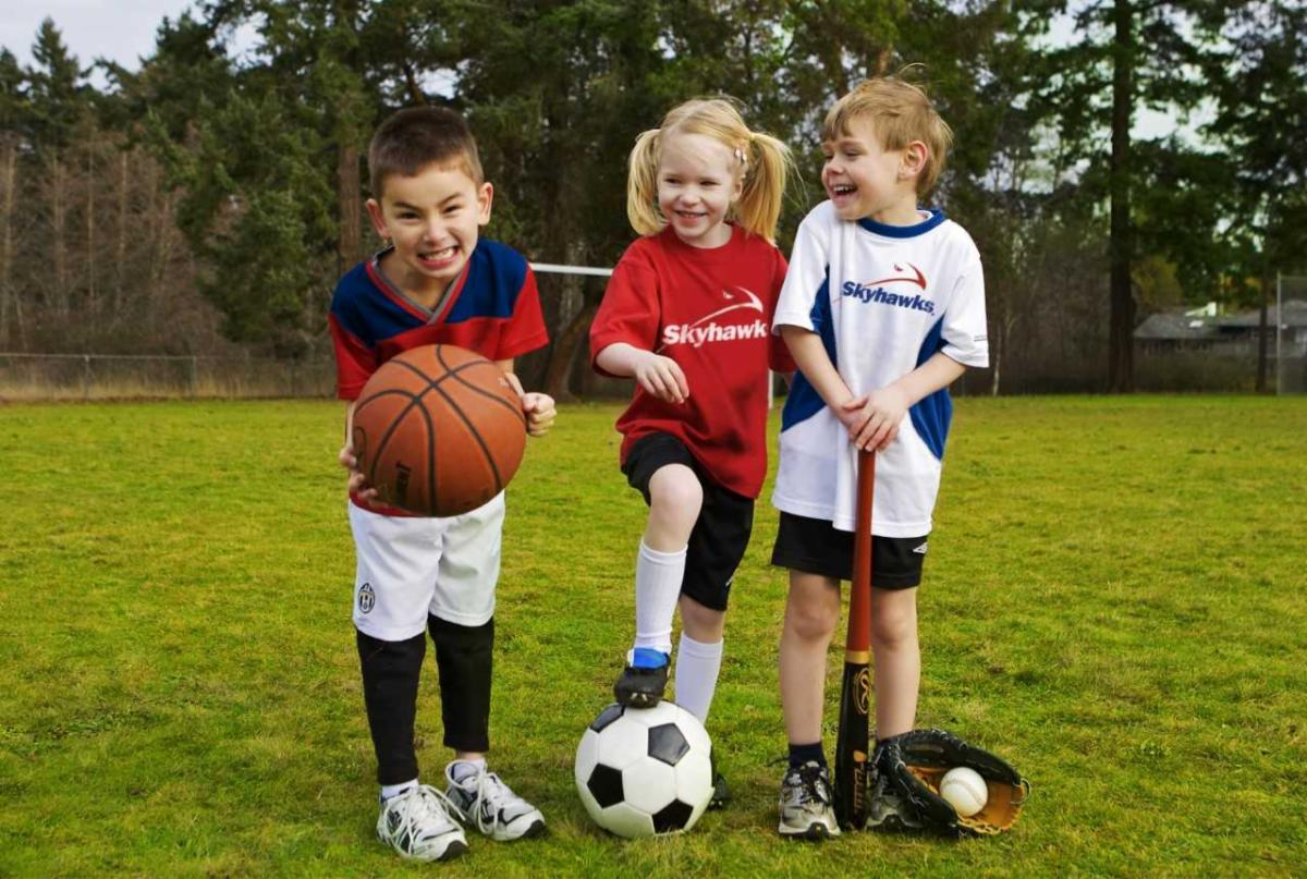 kids on grass with sports equipment