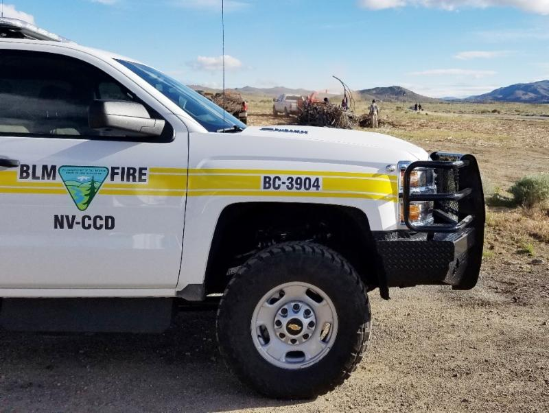 A Bureau of Land Management vehicle parked in front of crews chipping woody vegetation.