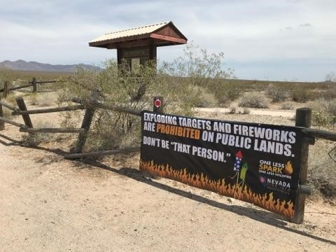 A banner hangs on a wooden fence in a desert landscape. Banner text reads - Exploding targets and fireworks are prohibited on public lands. Don't be 'that person.'