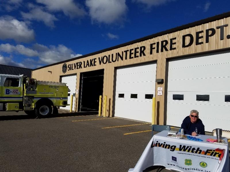 A volunteer sits at the Living With Fire display table in front of the Silver Lake Volunteer Fire Department building.