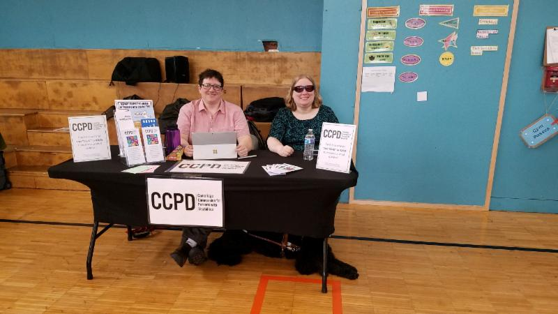 CCPD staff Kate & Rachel sitting at a CCPD informational table inside a gymnasium