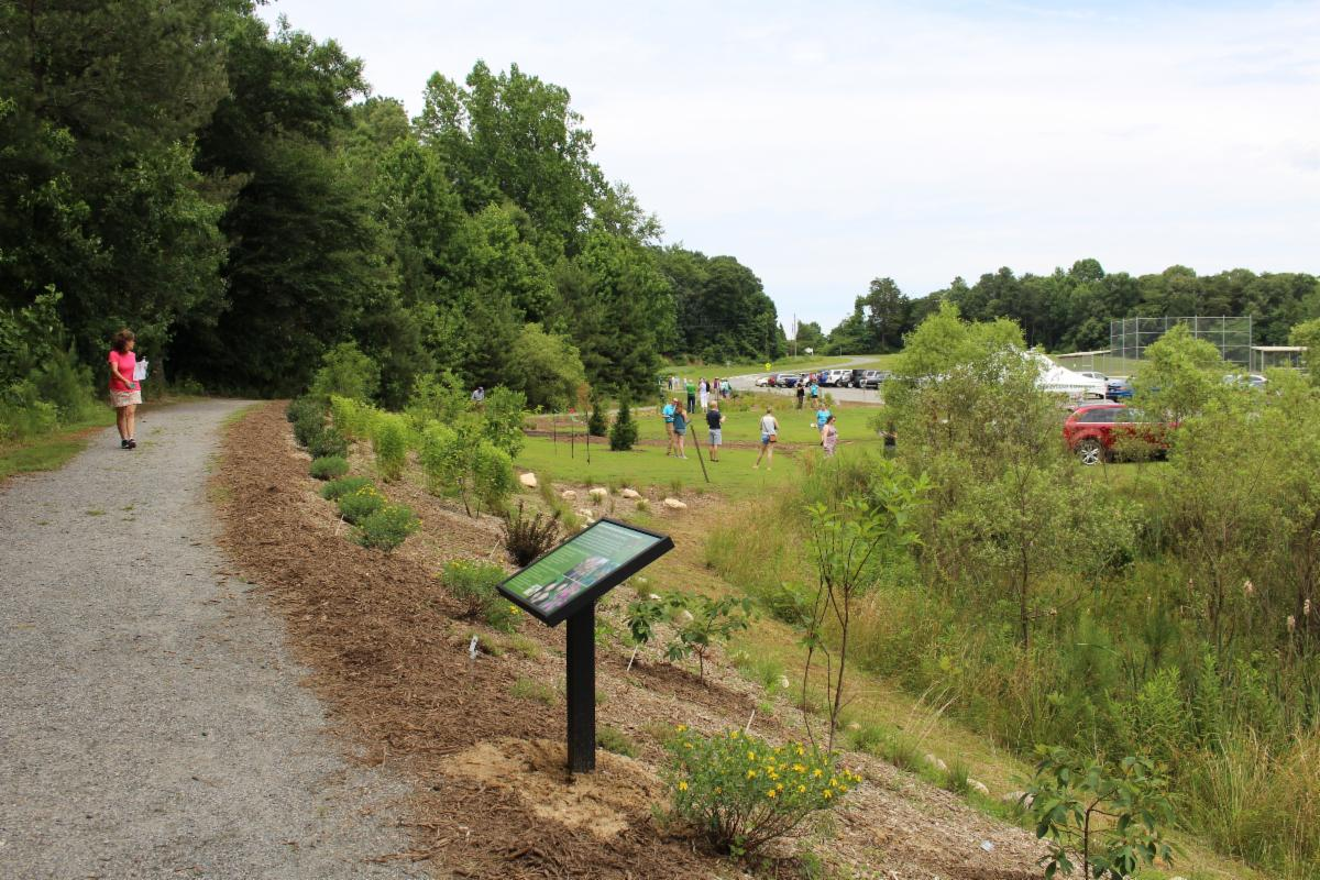 photograph of people planting a new landscaping area in background, interpretive sign in foreground