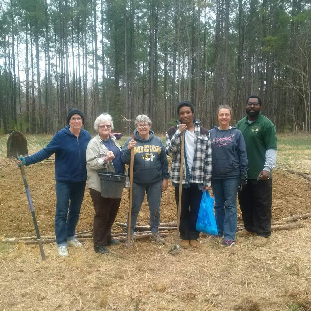 six people outdoors with garden tools