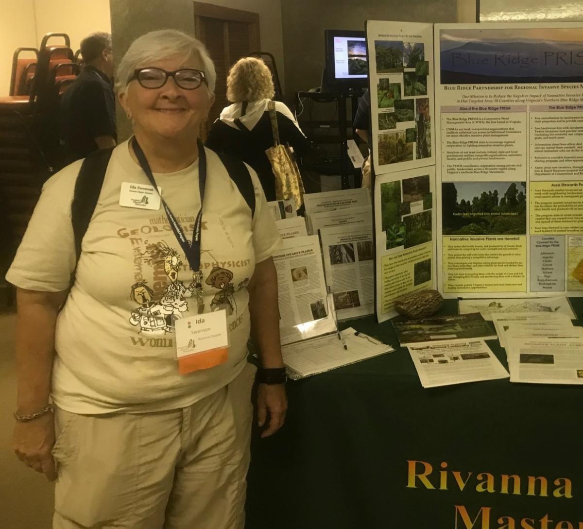 Photo of woman wearing Virginia Master Naturalist nametag, standing next to Rivanna Master Naturalist display table.