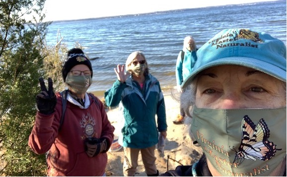 four people on a beach wearing masks with the Virginia Master Naturalist program logo