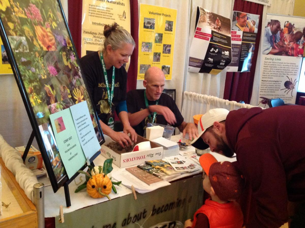 two people at a table displaying information about plants and pollinators, talking to a man and child