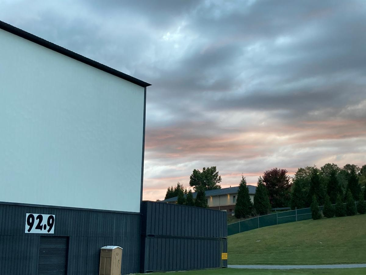 drive-in movie screen in foreground, sunset in background
