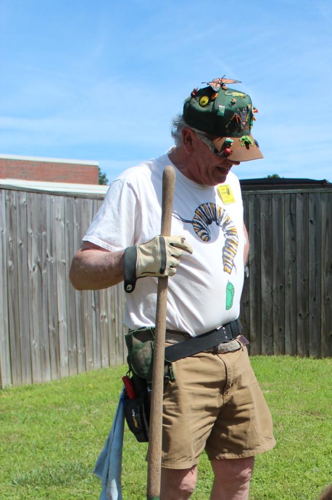 photo of Bill outdoors holding a garden tool