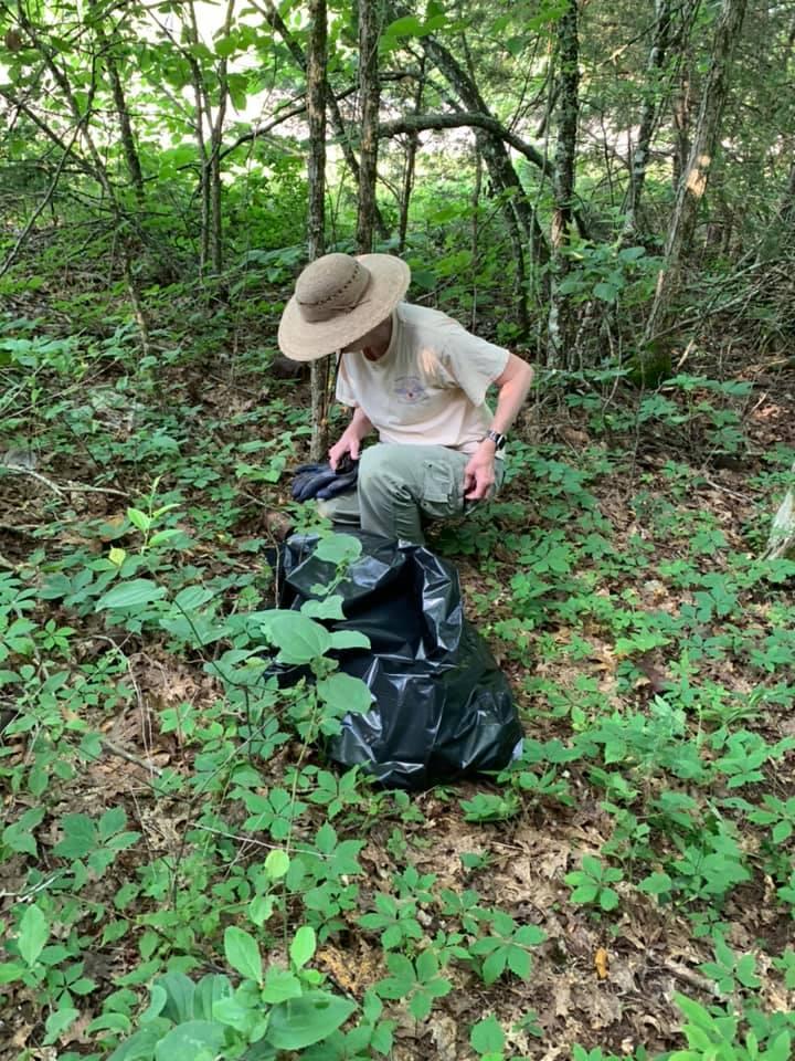 volunteer picks up trash in the forest