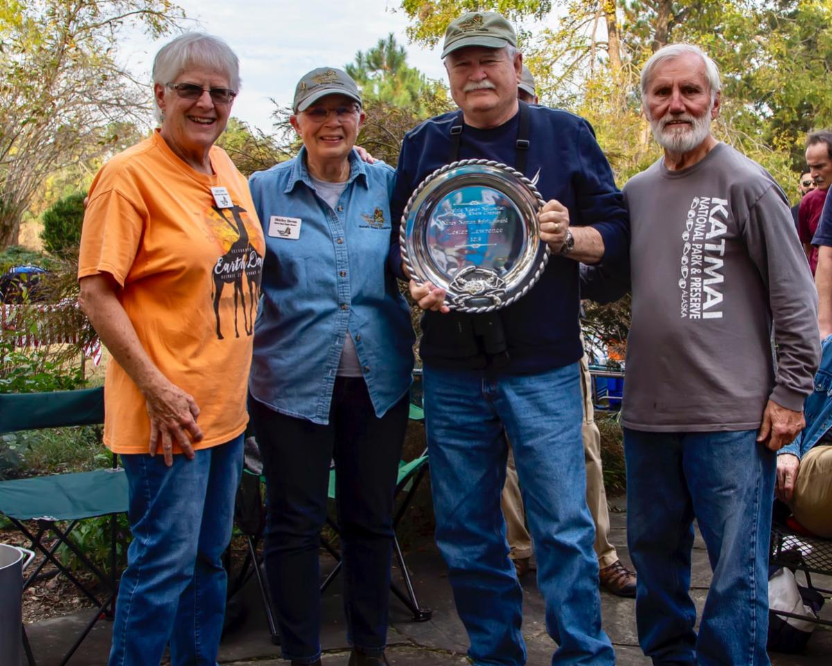 VMN volunteer Les Lawrence holding a large silver award platter with a crab on it, standing with three other volunteers outside.
