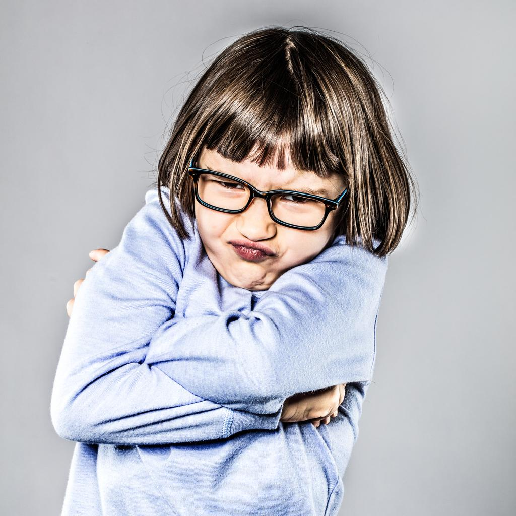 A little girl with bangs and eyeglasses, with her arms tightly crossed, and a very cute and frustrated expression.