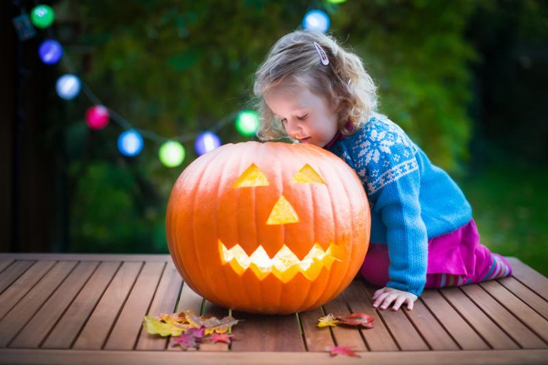Little girl carving pumpkin at Halloween. Dressed up child trick or treating. Kids trick or treat. Child in witch costume playing in autumn park. Toddler kid with jack-o-lantern.