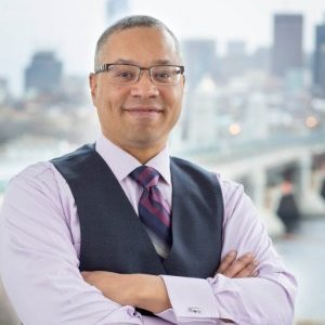 Dr. Dennis Dean portrait in bust_ with arms folded across his chest and smiling at the camera_ and a cityscape with bridge and skyscrapers shown somewhat out of focus in the background.