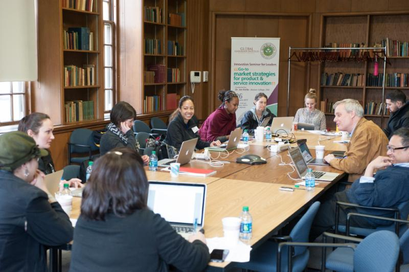 Group of twelve individuals shown seated indoors in a library at a long conference table with laptops_ notebooks_ and conference phone. Individuals are either looking at laptops or across the table at one another_ smiling warmly.