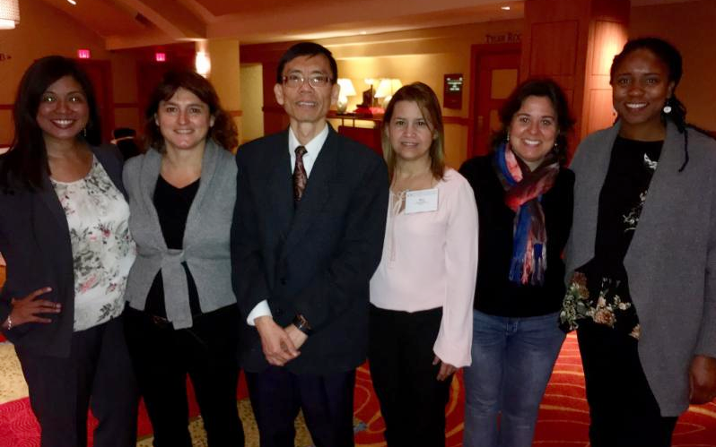 Dr. Hon Yuen stands with mentees at a research event.