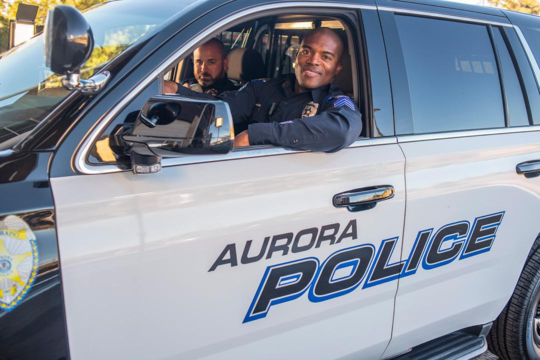 Aurora Police officer smiling from inside police car